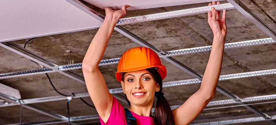 Woman in builder uniform and orange helmet installing suspended ceiling